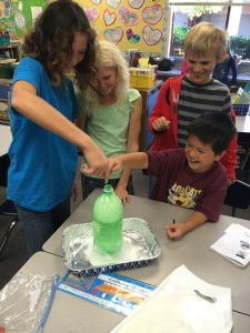 Dorothea Lange students explore a volcano made from baking soda and vinegar while learning about igneous rocks.